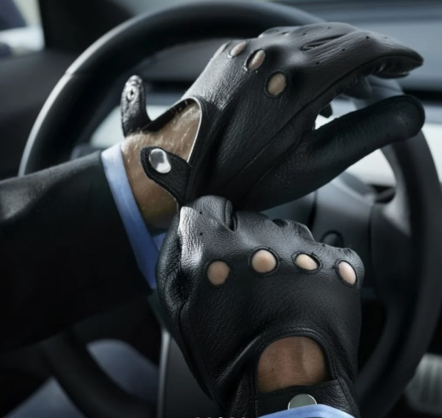 A pair of hands wearing the gloves whilst holding onto a steering wheel.