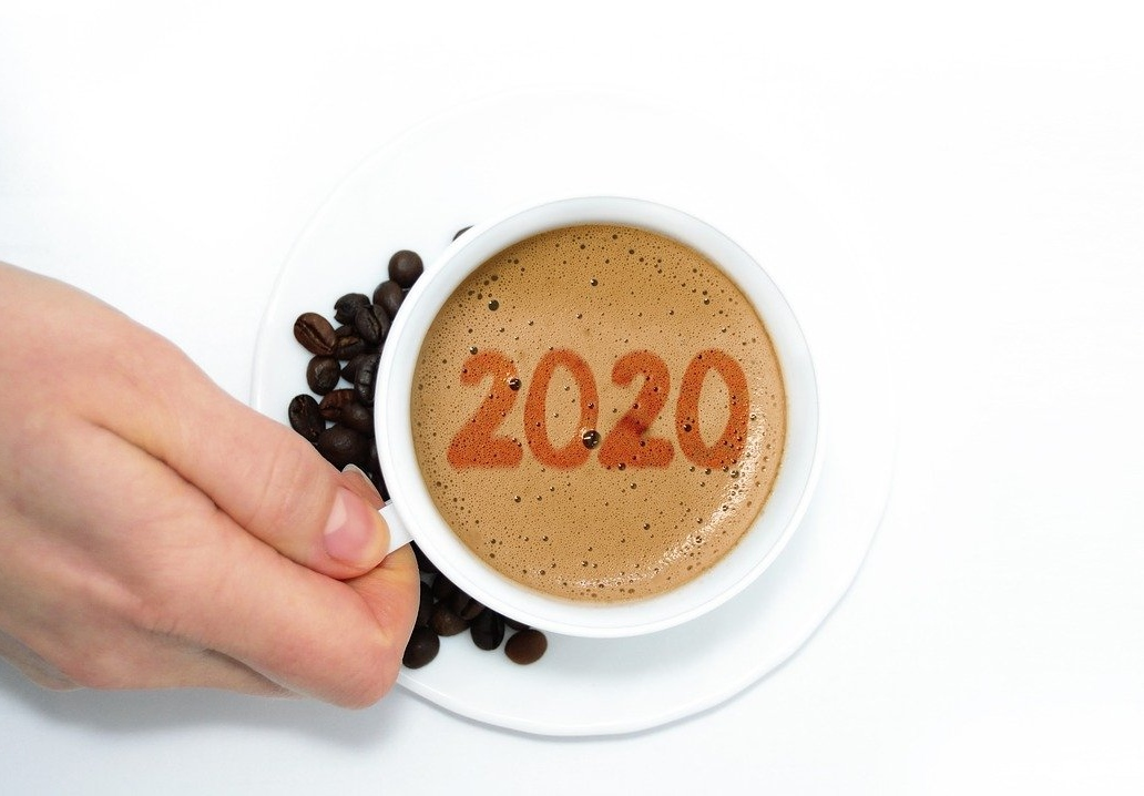 Hand holding a cup with 2020 in the coffee foam