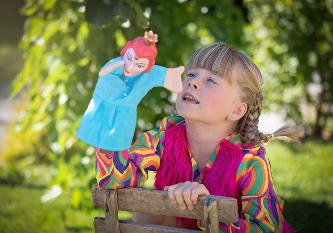 girl sitting on the grass with a hand puppet.