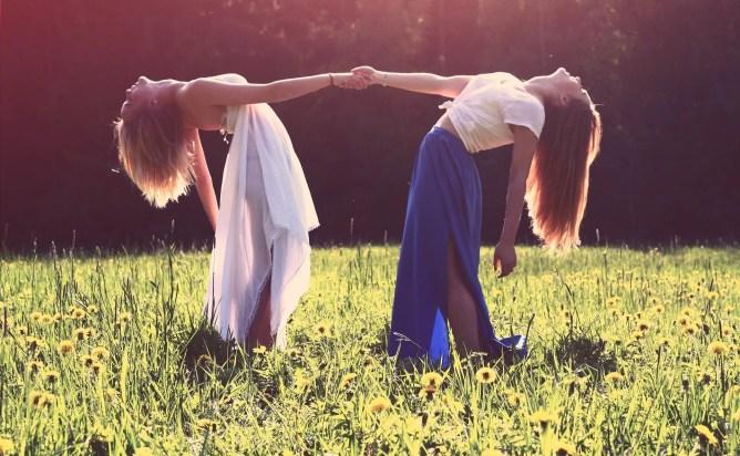 Two women holding hands amongst a field