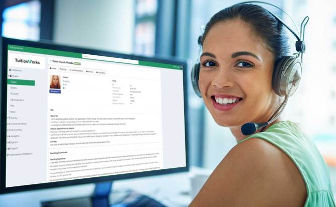 A smiling woman sitting in front of a computer which has a TuitionWorks screen in the background.