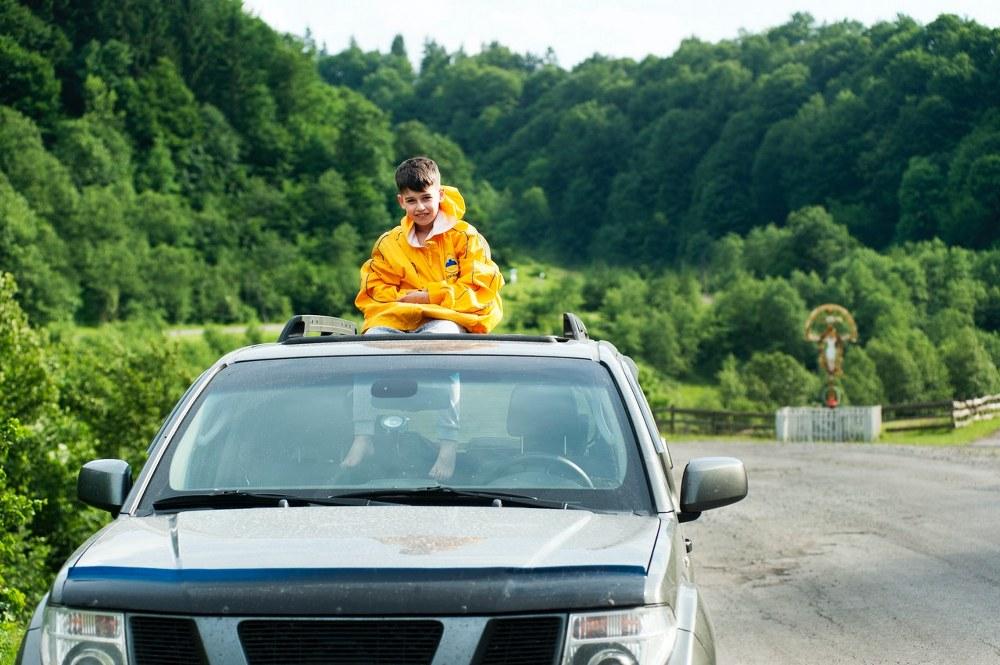 kid sitting on car roof on road trip