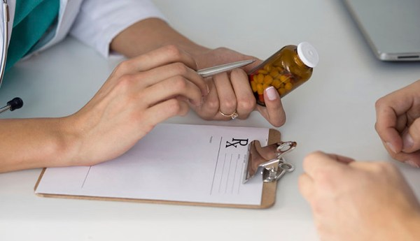 Close-up view of female doctor's hand holding bottle with pills and writing prescription. Healthcare, medical and pharmacy concept.