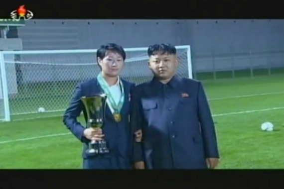 A female athlete posing for a memorial photo with Kim Jong-un | Image: 경애하는 김정은원수님께서 여러부문 사업을 현지에서 지도 주체102, 7 (2013), Youtube.