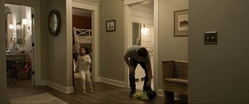 床に脱ぎ捨てられた服を拾う夫