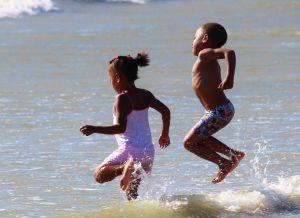 enfants en maillot sautant dans les vagues