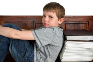 enfant qui appuie son dos sur une pile de livres de grammaire, l'air boudeur
