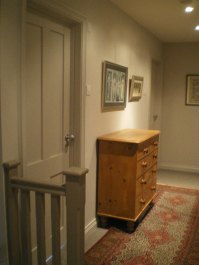 The doors have been painted the same colour as the walls to avoid the 'corridor' look. Useful storage in the chest of drawers and colour added with a runner.