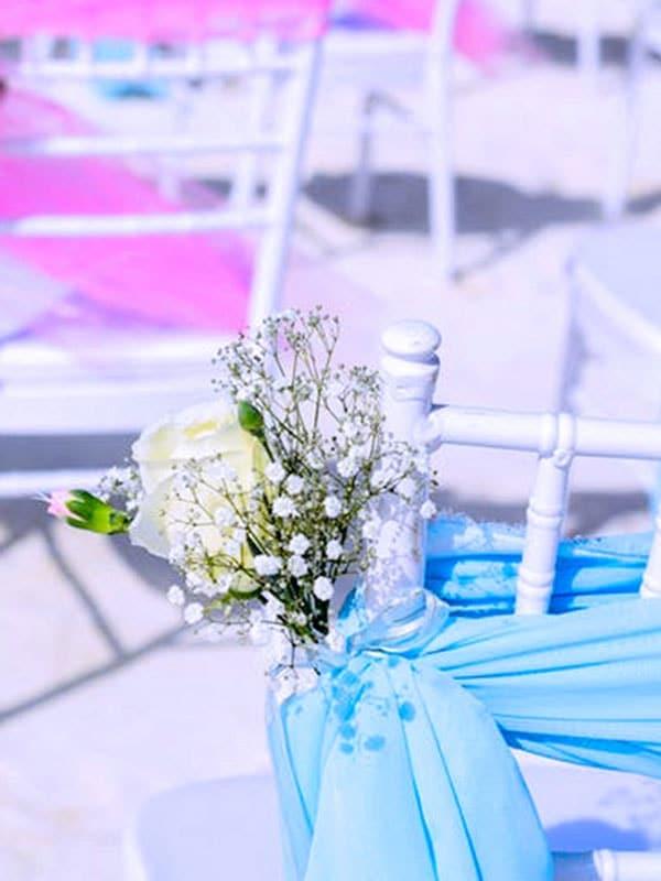 wedding reception small beach wedding destination pink ribbon chairs min