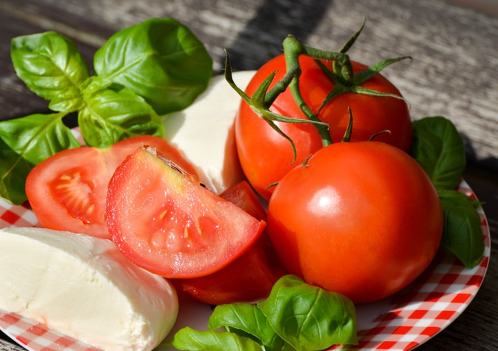 fresh ingredients in a bowl ready to be cut for a caprese salad with tomato on the vine, basil and mozzarella