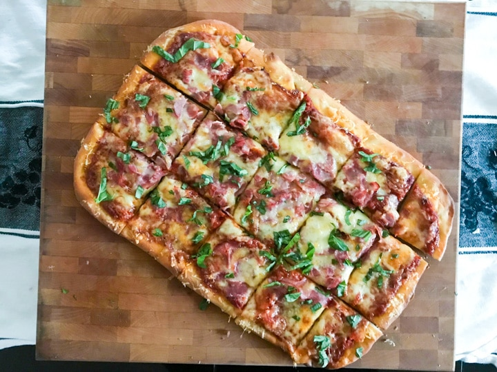 homemade pizza topped with ham cheese and basil shaped in a rectangle cooling on a butcher block
