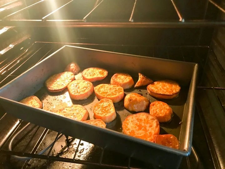 sliced sweet potatoes in a rimmed baking sheet in the oven