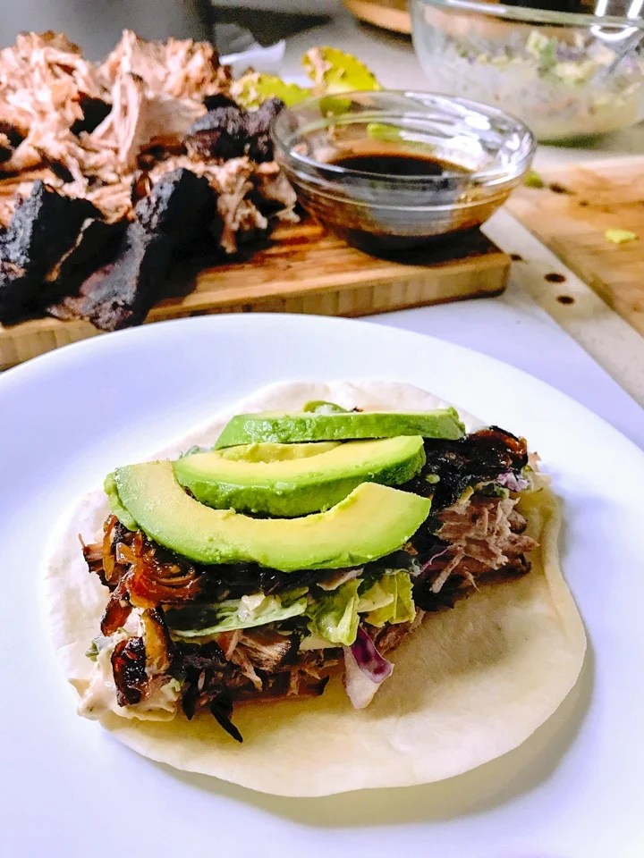 sous vide pulled pork shredded in a flour tortilla on a white plate with avocado