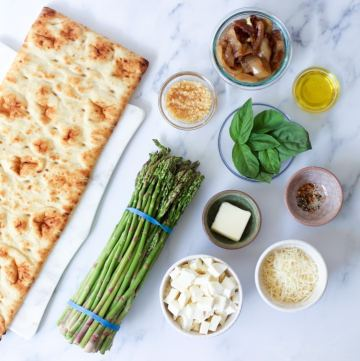 ingredients for asparagus pizza including pizza crust, pesto, mozzarella, caramelized onions, basil, parmesan cheese, butter, salt and pepper