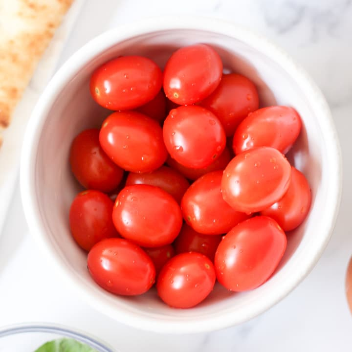 fresh raw cherry tomatoes in a white bowl