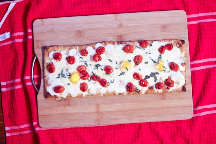 Finished brunch pizza baked in the oven with soft eggs on a cutting board