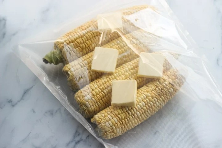 preparing sous vide corn on the cob with butter and salt