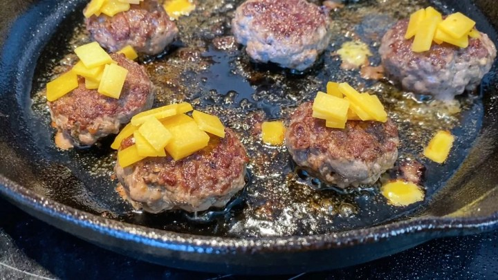 mini ground beef patties cooking in cast iron skillet