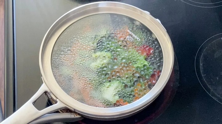 steaming vegetables in a pan on the stove with water and a pot cover