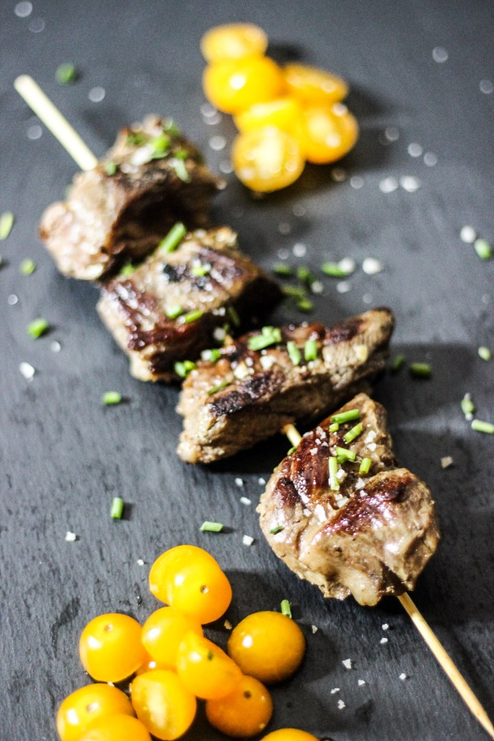 sous vide beef kebabs on a skewer with tomatoes