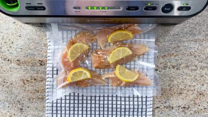 vacuum sealing sous vide chicken with lemons