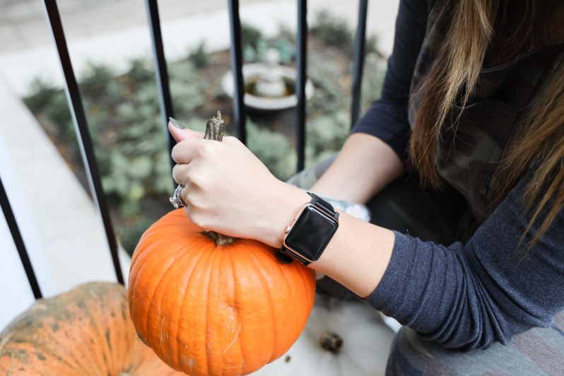 woman picking up pumpkin with Apple Watch on wrist