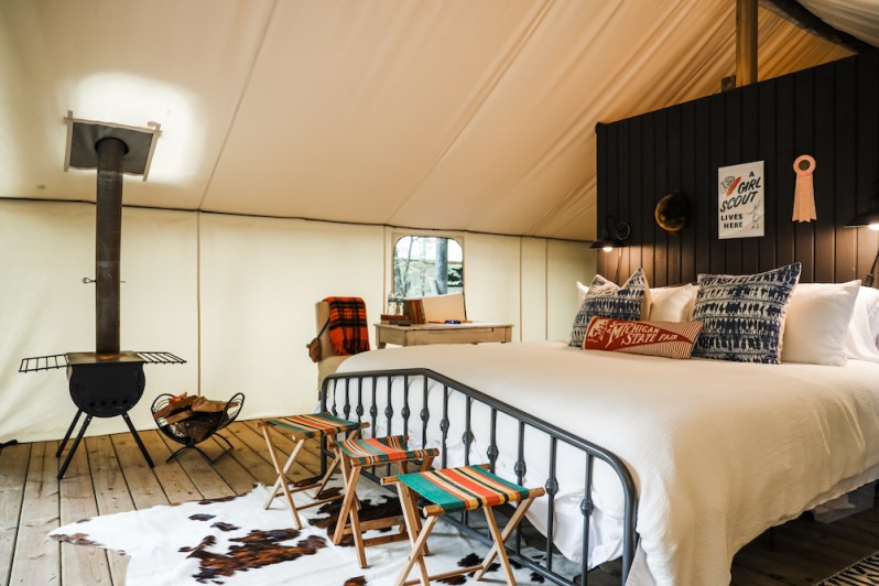 Interior of Glamorous Tent King Bed Stools Wood Burning Fireplace