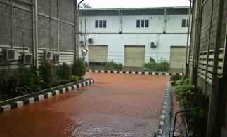 Air berwarna coklat menguasai jalan...