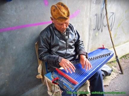 Pemain kecapi di Gang Bale Desa.