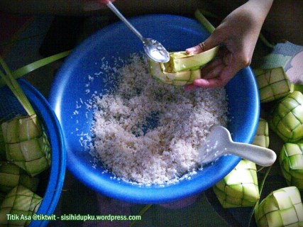 Memasukkan beras kedalam cangkang ketupat.