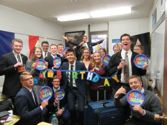 a-large-numbe-rof-the-departing-missionaries-elder-vosniks-birthday-center-holding-banner
