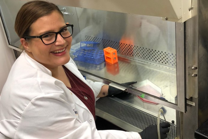 Dr. Christa Trexler in a lab coat, seated, in cell culture