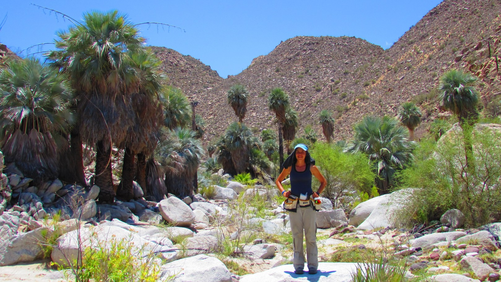 Lorena standing in the desert in Berrendo with tools around her belt and a hat to protect her from the sun.