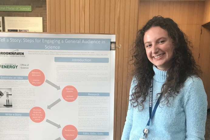"A smiling person (with curly hair, a blue sweater, and a lanyard around her neck) stands next to a poster with the title ""Tell a story: steps for engaging a general audience in science"""
