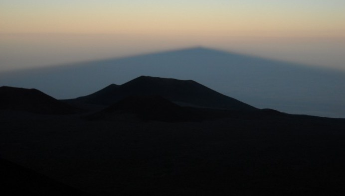 Maunakea Summit, facing East -- a dark silhouette of a mountain peak with a soft blue/grey and yellow sky in the background.