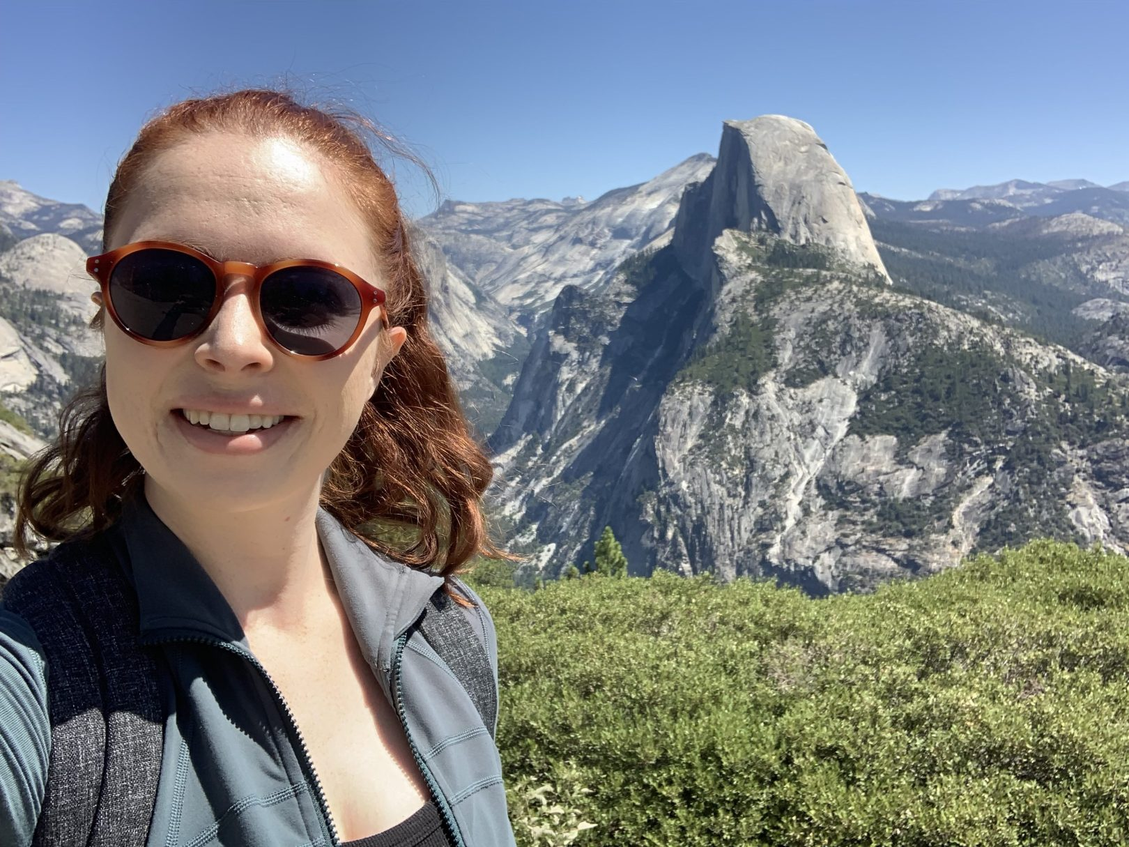 Selfie of the author wearing sunglasses, a backpack, and athletic clothes with gray mountains and greenery in the background.