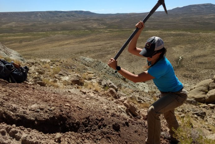 ft: A woman swings a pickaxe at rocks on a slope in the desert. A view of Wyoming's Red Desert, with red and tan striped rocks covered by pine trees.