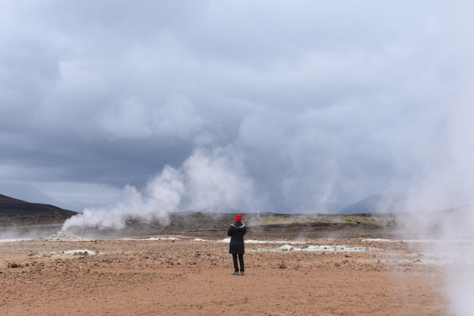 A person standing alone in front of a sulphur spring.