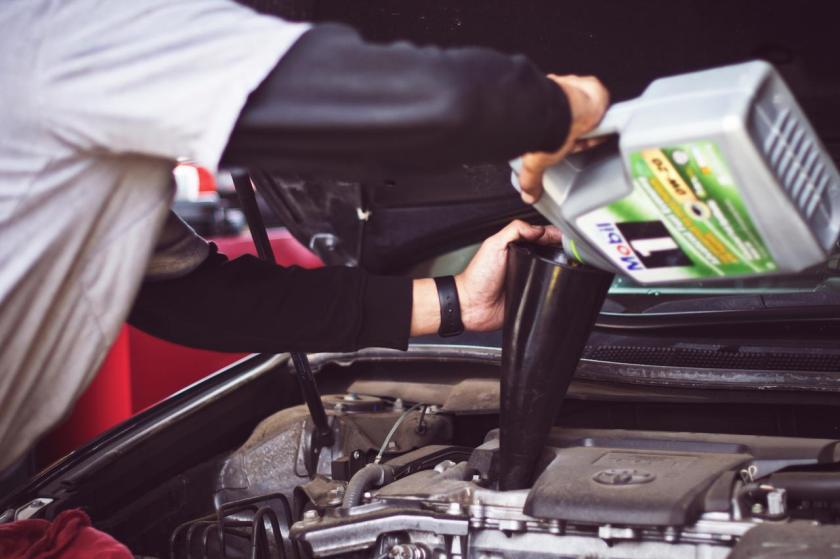 mecanico faz a troca de oleo do motor de um carro