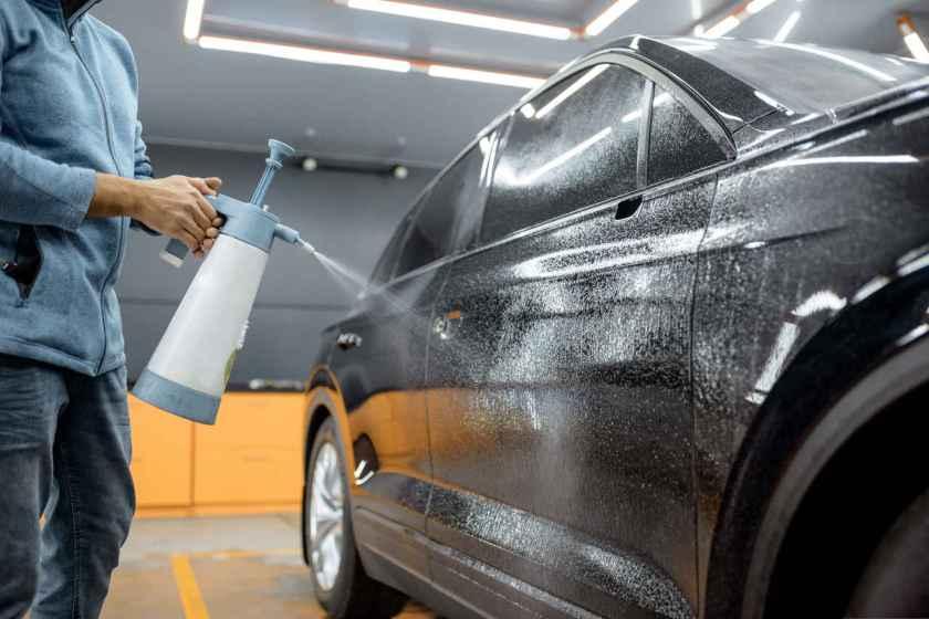 homem lava seu carro a seco na garagem do seu apartamento