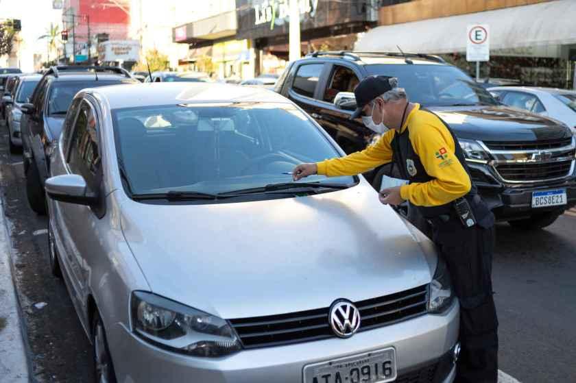 agente de transito multa motorista por estacionamento irregular