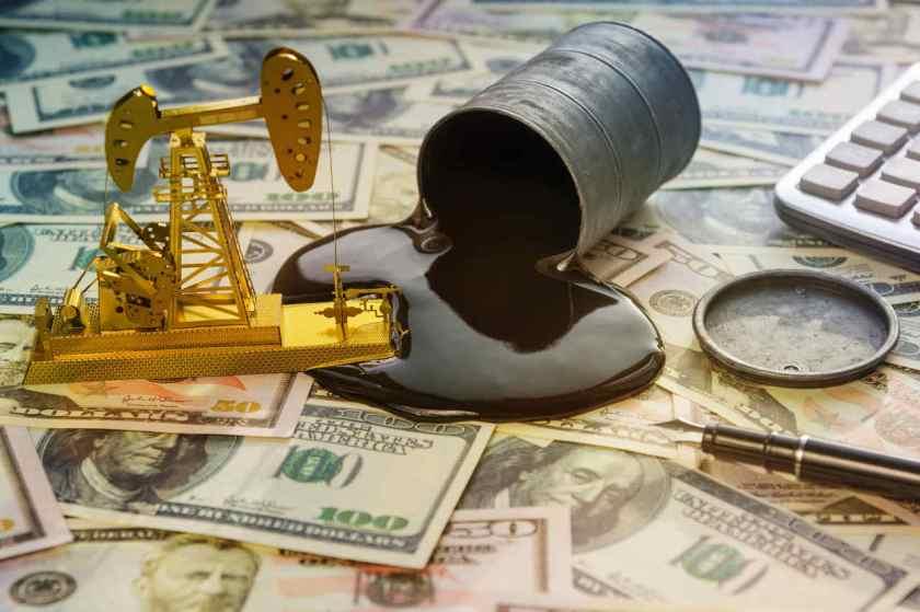 pequeno barril de petroleo derramado sobre notas de dólares ao lado de equipamento de refinaria