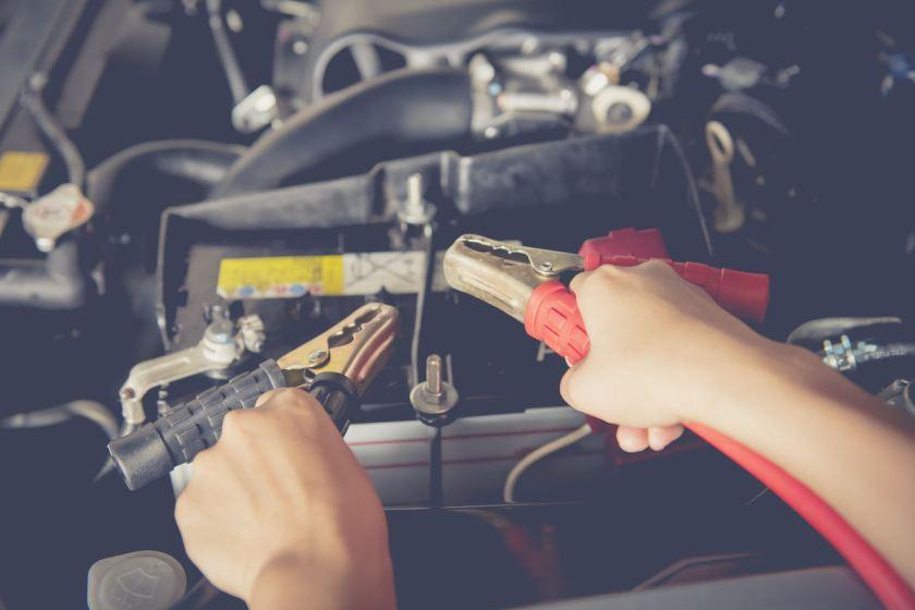 motorista conecta cabo de energia na bateria arriada do carro