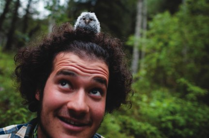 Colorado College Flammulated Owl student researcher Max Ciaglo sits with a baby owl on his head before taking the mass and measuring the flight feathers of the owlet.