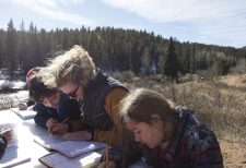 Ella Hartshorn '20 works with students on their bar graphs based on their animal scat findings which was the basis for her students' environmental education inquiry. Hartshorn's outdoor classroom was near a lake and the Catamount teepee.
