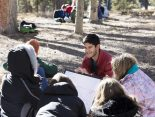 "Nathan Agarwal '19 reviews a lesson on global warming with students in the shade of the trees at the Catamount Center during the winter ecology part of the semester. ""Teaching them about this is so important, "" said Julie Francis, executive director of the Catamount Center. ""They are our future and hopefully they will be able to vote and make a change in the future."""