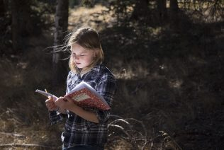 Columbine Elementary School student Lilli Eckstrom works in her scientific notebook during her outdoor school class on trees and quadrants.
