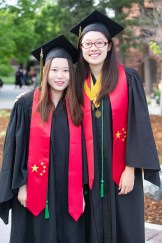 Yuhan Chen, left, and Tianran Zhang represent their home country of China by wearing a stole with the Chinese flag on it.