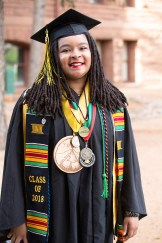 Atiya Harvey sports a TREE Semester medal, a medal for being a residential life advisor, a teaching and research medal, a medal representing the labyrinth provided by the Chaplain's Office, a Black Student Union stole, and a token to remember her recently deceased grandmother.