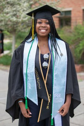 Sabre Morris wears stoles for Collaborative Community Engagement Scholar, President's Council, and Delta Gamma, a green cord for donation to the senior class gift, and a pin for S.A.I.L. Mentoring.